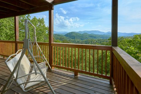 Cabin with porch swing overlooking mountain view - A Lazy Bear's Hideaway