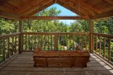 Rustic cabin with a porch swing and wooded view