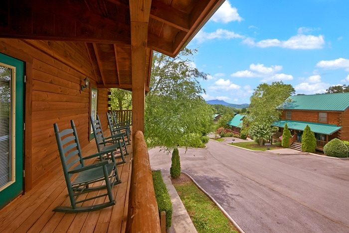 Cabin with rocking chairs and resort pool - Timber Lodge